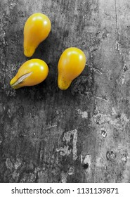 Three yellow cherry tomatoes on distressed table