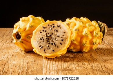 Three yellow dragon fruits placed on a wood table with a black background.  One of the fruits is sliced in half.