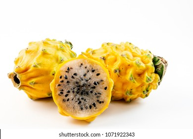 Three yellow dragon fruits placed in a pile isolated on a white background.  one of the fruits is sliced in half.
