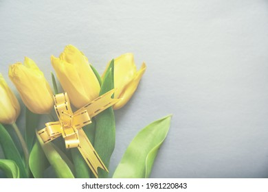 Three yellow fresh tulips on a silver grey background with a yellow ribbon and copy space. Concept of holiday, March 8, International womans day. Card with copy space. Colors of the 2021 year