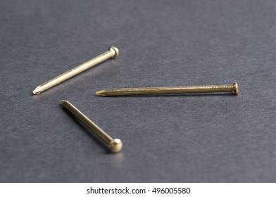three yellow iron nails, black isolated closeup