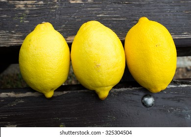 Three Yellow Lemons On Wooden Background