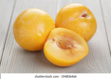 three yellow plums on rustic table, wood surface