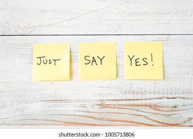three yellow Post It notes with message Just Say Yes! against weathered white wood background