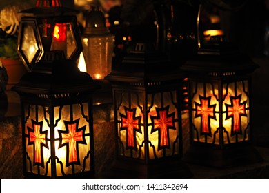 Three yellow and red grave candles standing in a row in a cemetery at night. Square lanterns with crosses burning bright on a grave during All Souls Day. Memory of the deceased concept.