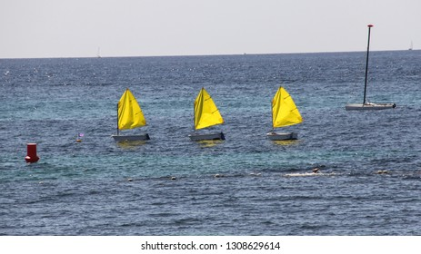 Three Yellow Sails on small boats floating on the Mediterranean