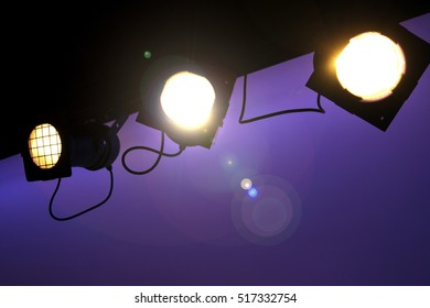 Three yellow stage light hanging on the ceiling
