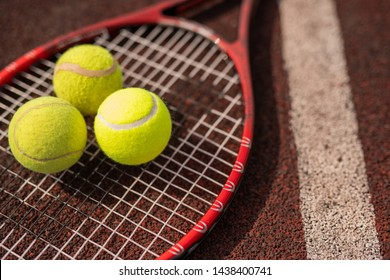 Three yellow tennis spheres lying on racket by white line