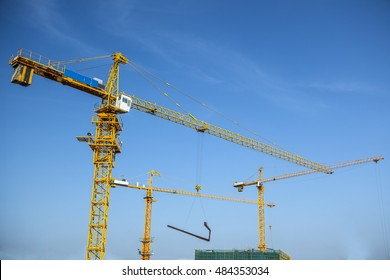 three yellow tower cranes in cooperative operation at a construction site