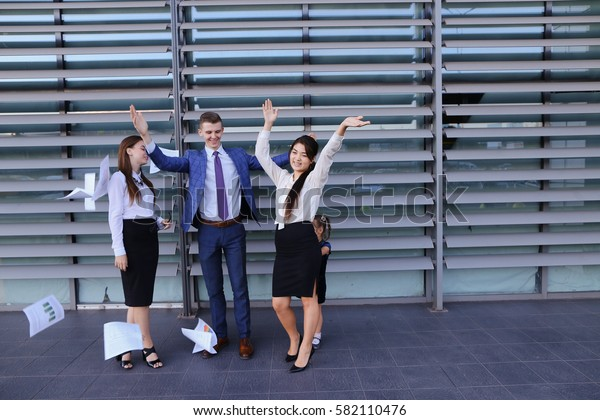 Three young adult attractive people, two women and one men students, prospective entrepreneurs  scatter paper and rejoice success, implementation of annual of business plan, end of working da