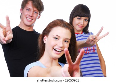 Three young adult people laughing and giving the victory sign.