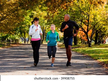 Three young adults jogging in the park