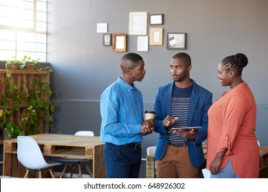 Three young African office coworkers smiling and talking together over a digital tablet while standing in a large modern office