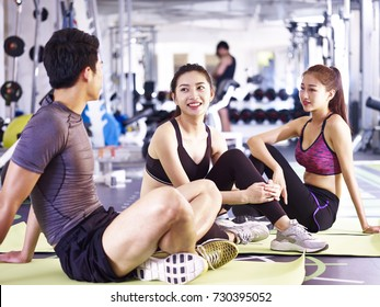 three young asian adult man and women sitting on floor resting relaxing talking during workout.