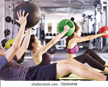 three young asian adult people working out in fitness center using medicine balls.