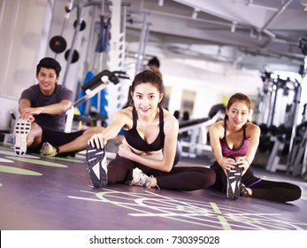 three young asian adult people exercising in gym stretching legs.