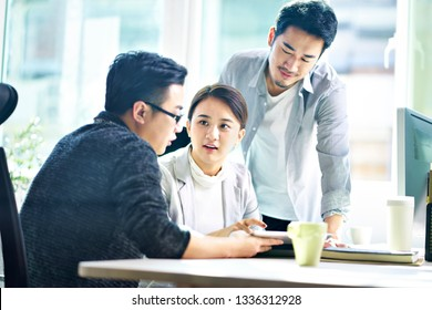 three young asian corporate executives meeting in office discussing business using digital tablet.