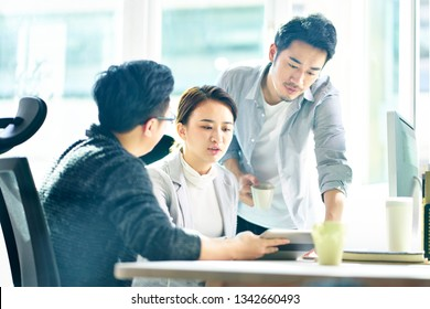 three young asian corporate executives working together discussing business plan in office.