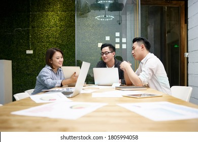 three young asian entrepreneurs meeting in office discussing business