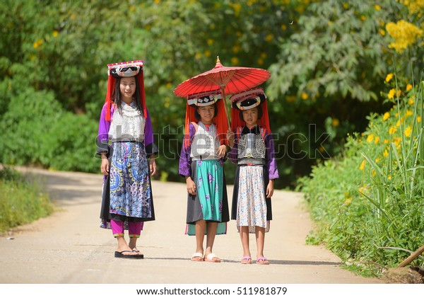 Three young asian Lahu tribe in custom dress,standing and smile among sunlight.