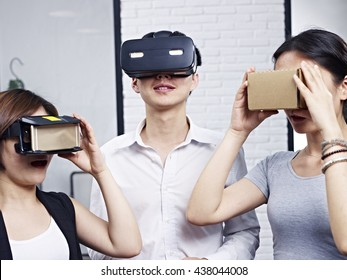 three young asian people wearing different types of virtual reality (VR) goggles.