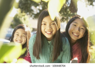 Three young Asian sisters smiling outdoors