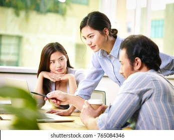 three young asian teammates businesspeople meeting discussing business in office, focus on person in the middle.
