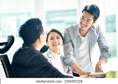 three young asian teammates working together having a pleasant business discussion in office.