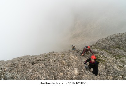 three young attractive male and female mountain climbers on a steep and exposed Via Ferrata in Alta Badia in the South Tyrol in the Italian Dolomites