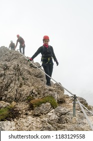 three young attractive male and female mountain climbers on an exposed Via Ferrata in Alta Badia in the South Tyrol in the Italian Dolomites