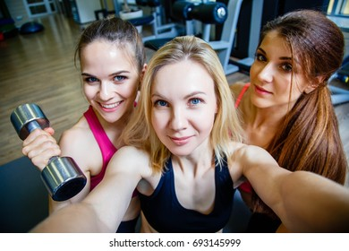 Three young attractive women doing selfie in the gym
