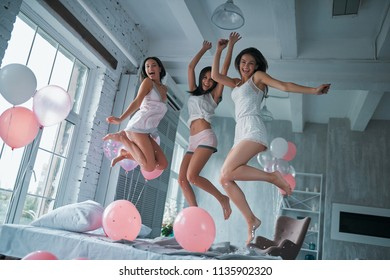 Three young attractive women are having fun at home in bedroom. Girls' pajamas party. Jumping on bed together.