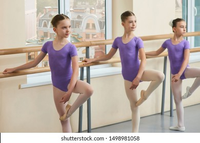 Three young ballerinas posing at ballet barre. Beautiful ballet dancers practicing dance move in studio hall. Lovely teen ballerinas.