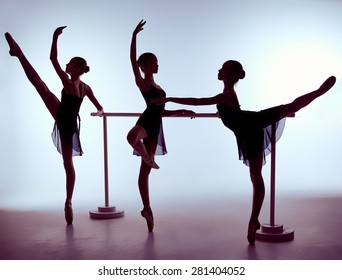 Three young ballerinas stretching on the bar on lilac background. The outline shooting - silhouettes of girls.