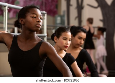Three young ballet dancers in a dance studio