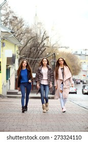 Three young beautiful girlfriends in autumn clothes walking down the street