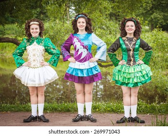 Three young beautiful girls in irish dance dress and wig posing outdoor