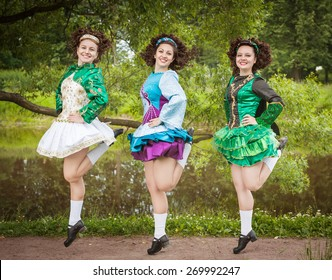 Three young beautiful girls in irish dance dress and wig dancing outdoor
