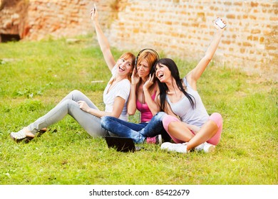 Three young beautiful girls listen music from notebook outdoor