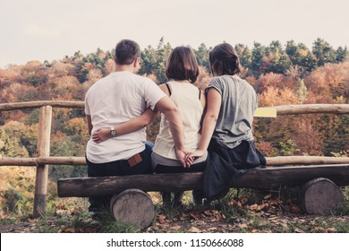 Three young beautiful people sit on a wooden bench and enjoy the autumn forest tree landscape, the concept of a love triangle, betrayal and treachery