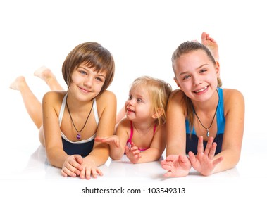 Three young beautiful sisters in swiming wear. Isolated over white background.