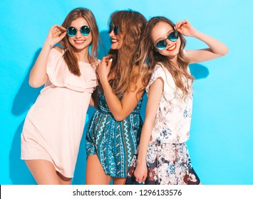 Three young beautiful smiling hipster girls in trendy summer colorful dresses. Sexy carefree women in sunglasses isolated on blue. Positive models going crazy