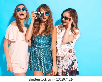 Three young beautiful smiling hipster girls in trendy summer casual dresses. Sexy carefree women posing near blue wall. Taking pictures on retro camera