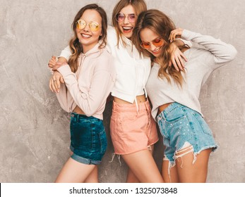 Three young beautiful smiling hipster girls in trendy summer sport clothes. Sexy carefree women posing near gray wall. Positive models in round sunglasses having fun. Hugging