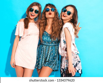 Three young beautiful smiling hipster girls in trendy summer casual dresses. Sexy carefree women posing near blue wall in round sunglasses. Having fun
