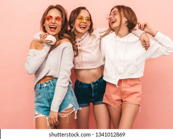 Three young beautiful smiling hipster girls in trendy summer hipster clothes. Sexy carefree women posing on pink background. Positive models having fun