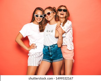 Three young beautiful smiling hipster girls in trendy summer clothes. Sexy carefree women posing near pink wall in studio. Positive models going crazy and having fun. In sunglasses