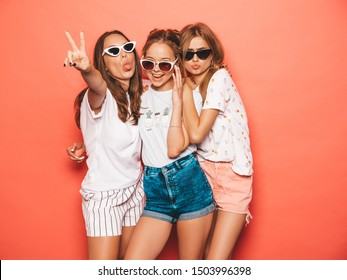 Three young beautiful smiling hipster girls in trendy summer clothes. Sexy carefree women posing near pink wall in studio. Positive models going crazy and having fun in sunglasses