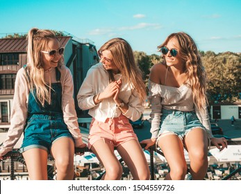 Three young beautiful smiling hipster girls in trendy summer clothes.Sexy women sitting on handrail in the street.Positive models having fun in sunglasses.They communicating and discussing something - Shutterstock ID 1504559726