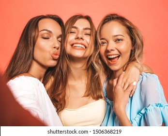 Three young beautiful smiling hipster girls in trendy summer clothes. Sexy carefree women posing near pink wall in studio. Positive models going crazy.Taking selfie self portrait photos on smartphone